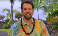Perillo Tours Hawaii Commercial thumbnail features Steve Perillo wearing a bright Hawaiian print shirt and a traditional black Kukui nut lei against a backdrop of beautiful Hawaiian trees and bushes (video production by Merging Media).