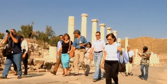 Perillo Tours Discover Israel commercial thumbnail features a group of Perillo Tours tourists walking along stone pillars that belong to the site of the once thriving ancient ruins of Israel (video production by Merging Media).