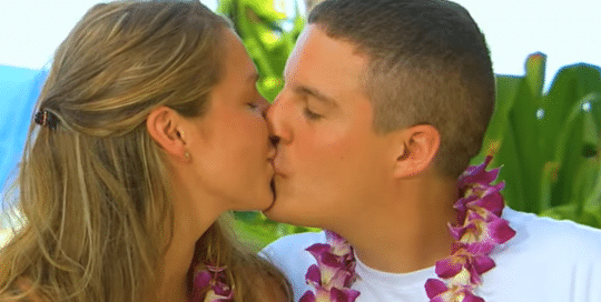 A young happy couple, on a Perillo Tours Discover Hawaii tour, kisses while wearing Hawaiian leis against a backdrop of Hawaiian foliage (video production by Merging Media).