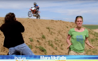 Host, Mara McFalls, stands in front of a sand dune that a motor bike rider drives fast on.