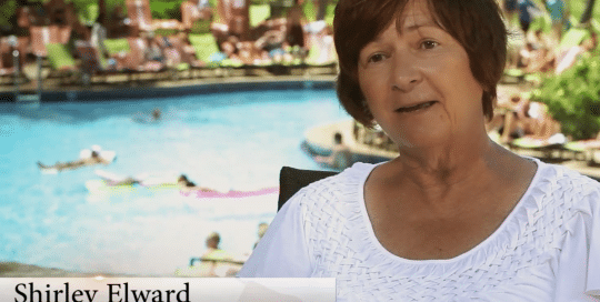Perillo Tours Hawaii Testimonials video thumbnail features an older woman sitting for an interview about her Hawaii Perillo Tour in front of a backdrop of a busy hotel pool, title on the bottom left labels her as Shirley Elward from Ipswich, MA (video production by Merging Media).