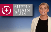 Commerical for Paper Products Supply Chain Plus a young woman with blonde pony tail wearing a cream blazer over a black top stand to the right of a sign that reads; SUPPLY CHAIN PLUS (video production by Merging Media).