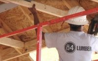 84 Lumber Construction Services video thumbnail features a man in a white tee-shirt and a white hard had with his back to the camera as he installs a roof joist, company logo on his shirt reads; 84 Lumber (video production by Merging Media).