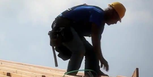 A man in a blue shirt and yellow hard hat, wears a tool belt while helping the 84 Lumber Joplin tornado rebuild in Missouri (video produced by Merging Media).