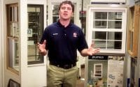 84 Lumber Windows How-To video thumbnail features host, Geroge, in his dark blue polo with the 84 Lumber logo on this left chest, standing in front of a display of different types of windows a homeowner can learn to install in the Windows How To Video (video produced by Merging Media).