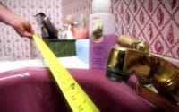 84 Lumber Bathroom How-To video thumbnail features an outdated bathroom with a brass faucet on a mauve sink and the wallpaper the same mauve as seashells against a white background is about to get measurements for a homeowner facelift in this How To Video (video production by Merging Media).