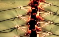 Birdseye view of a mens rowing team, wearing black tank top uniforms, in an eight person shell in Bobrick 2006 Vision Conference commercial