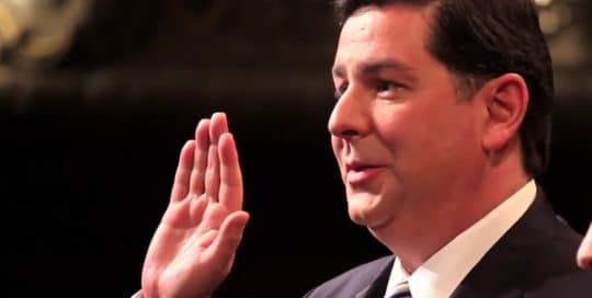 Mayor Peduto stands in his suit and tie at his inauguration with right hand in the air to be sorwn in as the mayor of Pittsburgh, Pennsylvania as recorded in Mayor Peduto Inauguration video (video production by Merging Media).