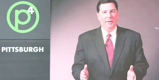 Mayor Peduto Fast Photo P4 Conference; Mayor Peduto stands in a black suit with a white shirt and red tie next to words that read P4 Pittsburgh (video production by Merging Media).