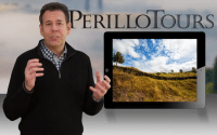 (Steve Perillo) Man wearing black half-zip sweater is standing next to a large image of an iPad with beautiful scene of a vacant Italian country side in this Perillo Tours Million Memories Commercial, text reads; Perillo Tours (video production by Merging Media)
