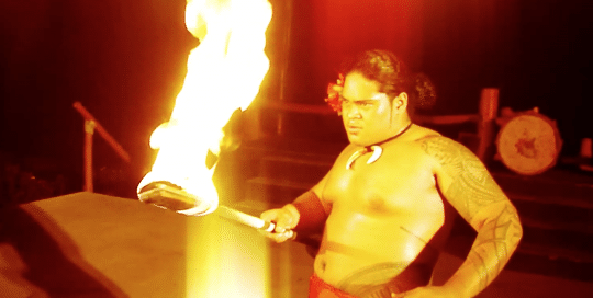 Hawaiian man with tattoos and traditional Hawaiian lava-lava attire, preforming the ceremonial fire knife dance at the Bobrick Fire & Knife Convention (video production by Merging Media).