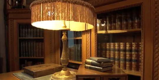 The Frick Building Pittsburgh video thumbnail sets the scene of a detailed antique styled glass enclosed bookcases set the backdrop for a intricate gold table lamp with a fringed shade set upon a wooden desk (video production by Merging Media).