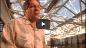 USWeb National Airlines Case Study video thumbnail is a man wearing a white button up answering interview questions about National Airlines against a back drop if an airport lobby, large white round beams crossing in front of a ceiling of windows.