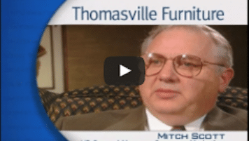 USWeb Solutions For The Information Age video thumbnail is an older gentleman with white hair and glasses with words below him labeling his name as Mitch Scott, sits for an interview, words above his head read; Thomasville Furniture.