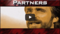 USWeb Velocity Opening Video thumbnail is of a face of a handsome man with dark hair and a beard, that is boarded top and bottom by a thick red border, word above the mans head reads; PARTNERS.