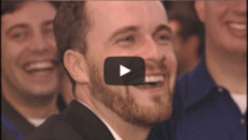 USWeb Velocity Closing Video thumbnail is of a man wearing a sport jacket with short hair and a beard is smiling and laughing while a few men in the background are doing the same.