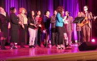 On stage, against a royal purple curtain, a casual choir sings behind a lead at the microphone accompanied by a acoustic guitar at the Mayor Peduto VIP Event Celebration (video production by Merging Media).