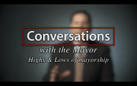 Mayor Peduto talks Mayorship; Blurred figure of a man in a suit sitting in front of a very dark blue background, the large word in the foreground in white text reads; Conversations with the Mayor, Highs and Low of Mayorship (video produced by Merging Media).