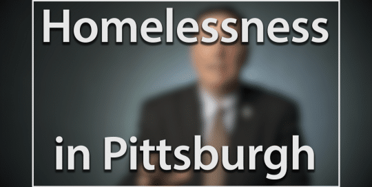 Mayor Peduto on Homelessness in Pittsburgh; Blurred figure of a man in a suit sitting in front of a very dark blue background, the large word in the foreground in white text reads; Homelessness in Pittsburgh (video produced by Merging Media).