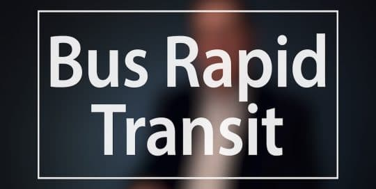 Mayor Peduto Bus Rapid Transit campaign; Blurred figure of a man in a suit sitting in front of a very dark blue background, the large word in the foreground in white text reads; Bus Rapid Transit (video production by Merging Media).