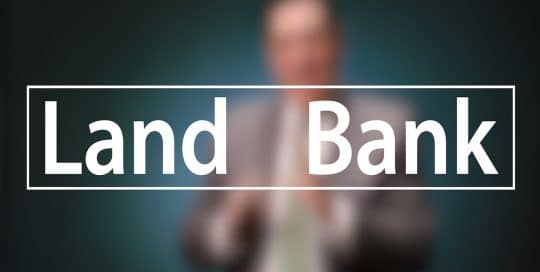 Mayor Peduto Landbank Campaign; Blurred figure of a man in a suit sitting in front of a very dark blue background, the large word in the foreground in white text reads; Land Bank (video produced by Merging Media).