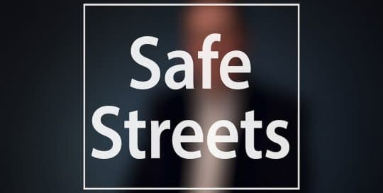 Mayor Peduto on Bike Lanes in Pittsburgh; Blurred figure of a man in a suit sitting in front of a very dark blue background, the large word in the foreground in white text reads; Safe Streets (video produced by Merging Media).