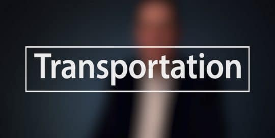 Blurred figure of a man (Mayor Peduto) in a suit sitting in front of a very dark blue background, the large word in the foreground in white text reads; Transportation (video production by Merging Media).