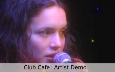Live at Club Cafe Artist Demo features a close up of artist Nora Jones singing into the microphone on the Club Cafe stage, words below her read; Club Cafe: Artist Demo (video production by Merging Media).