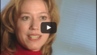 USWeb Tower Records Case Study video thumbnail is a close up of a woman with dark blonde hair wearing a red turtle neck sweater giving an interview on Towe Records against a background of a window covered with white mini blinds.