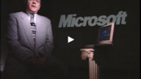 USWeb IE 4 Deployment video thumbnail is of an older gentleman wearing a gray suit with a black and gray tie, stands next to a 1990's style laptop set on an ionic style short pillar, word in background reads, Microsoft.