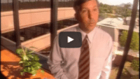 USWeb Honeywell Case Study video thumbnail of a man wearing a white button up dress shirt with a brown and red striped tie stands in front of an office building window with a wing of the building seen out the window view.