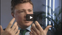 USWeb Haseldonckx Case Study video thumbnail is of a middle aged man wearing a black sport coat, gray button up shirt, and emerald green tie, sits down for an interview and is speaking with hands up in an emphasis gesture.